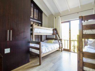 main house bunk bedroom with balcony views